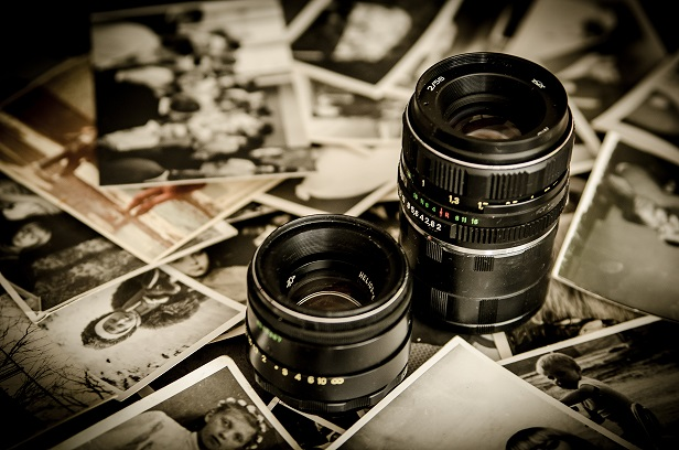 Camera lenses surrounded by photographs