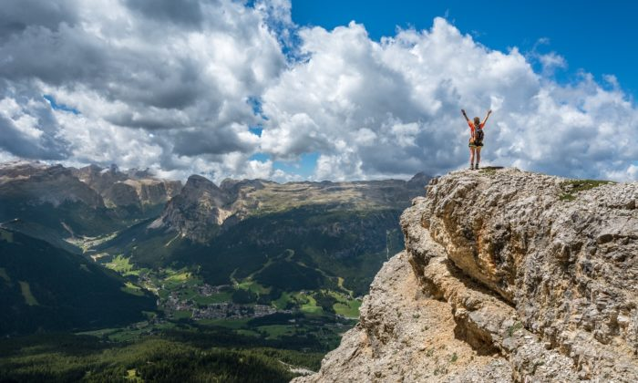 Woman standing on cliff overlooking mountain range