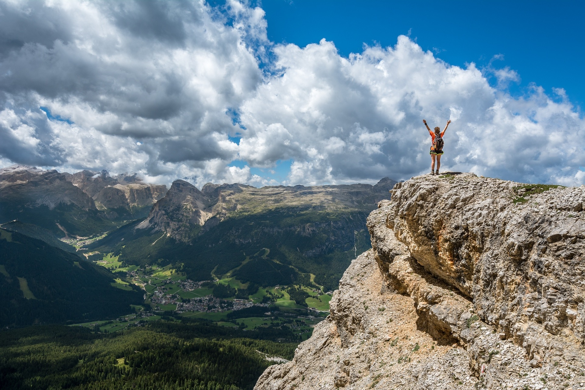 Woman standing on cliff overlooking mountain range